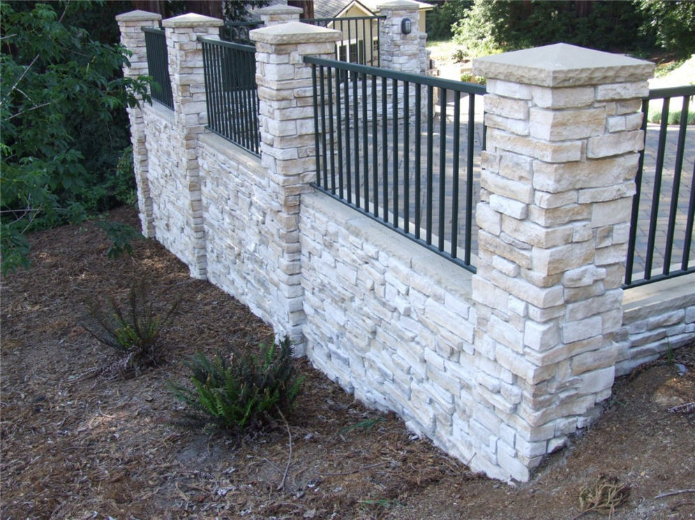 Stacked stone wall with metal fencing